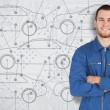 Young mechanic standing in front of cars background — Stock Photo