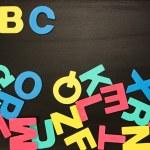 alfabetet magneter i ett virrvarr på tavlan med abc i ordning — Stockfoto