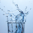 Close up on ice cube falling into glass of water — Stock Photo