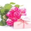 Bouquet of pink roses next to a gift with a happy birthday card — Stock Photo