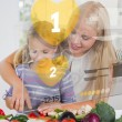 Mother and daughter chopping vegetables with yellow holographic - Stock Photo