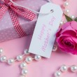 Pink rose with gift and string of pearls and tag for mothers day - Stock Photo