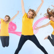 Three of the same young woman jumping for joy — Stock Photo