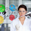 Stock Photo: Serious chemist working with colourful cell diagram inteface
