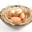 Three eggs in a black bowl with one gold one — Stock Photo