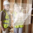 Architect and foreman checking the plans on white interface — Stock Photo