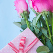 Bouquet of pink roses in vase with pink gift - Стоковая фотография
