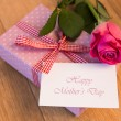 Pink wrapped present with happy mothers day card and pink rose — Stock Photo