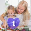 Mother and daughter chopping vegetables with purple holographic - Stock Photo