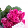 Bouquet of pink roses with happy mothers day card on a table — Stock Photo