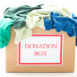 Cardboard donation box with clothes on white background - Stock Photo
