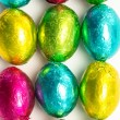 Colourful foil wrapped easter eggs overhead shot - Stock Photo