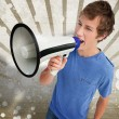 Young man shouting through a megaphone - Stock Photo