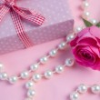 Pink rose with gift and string of pearls — Stock Photo