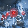 Stock Photo: Mechanic reparing car while consulting futuristic interface