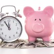 Pink piggy bank beside alarm clock on dollars — Stock Photo #24149169
