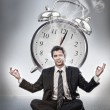 Businessman meditating in front of alarm clock — Stock Photo