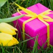 Pink gift box and yellow tulips — Stock Photo