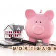 Piggy bank beside calculator, miniature house and mortgage spell — Stock Photo