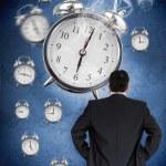 Businessman looking at wall of alarm clocks — Stock Photo