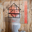 Man insulating walls following instructions on interface - Stockfoto