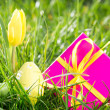 Pink gift box with easter egg and yellow tulip - Stock Photo