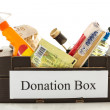 Black cardboard donation box with houseware product and food - Foto Stock