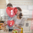 Happy couple making dinner using interface instructions - Stock Photo