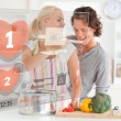 Cute couple making dinner using interface instructions — Stock Photo #24149753