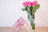 Bouquet of pink roses in vase with pink gift leaning against it — Stock Photo