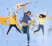 Young man with guitar and two girls jumping for joy — Stock Photo