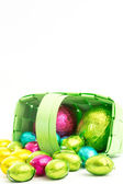 Foil wrapped easter eggs spilling from a basket — Stock Photo