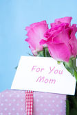 Bouquet of pink roses in vase with pink gift and mothers day car — Stock Photo