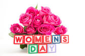 Bunch of pink roses next to wooden blocks spelling womens day — Stock Photo