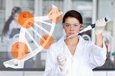 Pretty lab worker adding chemical to test tube — Stock Photo
