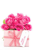 Bouquet of beautiful pink roses next to a pink gift with a happy — Stok fotoğraf