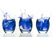 Serial arrangement of blue liquid splashing in tumbler — Stock Photo