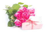 Bouquet of pink roses next to a gift with a blank card — Stock Photo