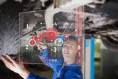 Mechanic under car consulting interface — Stock Photo