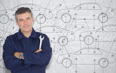 Mature mechanic standing in front of a cars diagram background — Stock Photo
