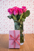 Bunch of pink roses in vase with pink gift leaning against it — Stock Photo