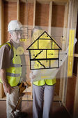 Architect and foreman standing behind house plan interface — Foto Stock