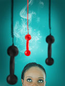Woman looking up at hanging telephone receiver — Stockfoto