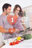 Smiling couple preparing dinner using futuristic interface — Stock Photo