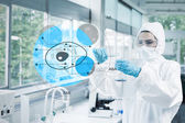 Scientist in protective suit working with cell diagram interface — 图库照片