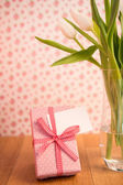 Vase of tulips on wooden table with pink wrapped gift and blank — Stock Photo