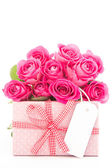 Bouquet of beautiful pink roses next to a pink gift with a blank — Stock Photo