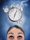 Woman looking up at ringing alarm clocks — Stock Photo