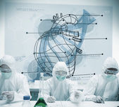 Chemists working with futuristic interface showing heart and DNA — Stock Photo