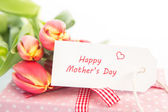 Bouquet of tulips next to a gift with a happy mothers day card — Stok fotoğraf